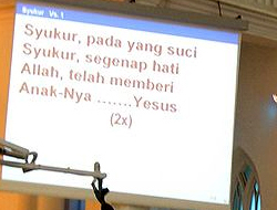 If you look closely at the screen displaying the text of a hymn being sung in a Malaysian Church,  you can see the word Allah and Jesus (Yesus) being used. Photo Malaysian Church, Wikipedia:Vmenkov