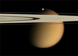 A photo of Titan taken by the Cassini spacecraft. Saturn's rings pictured in front of Titan. Photo Wikipedia/NASA