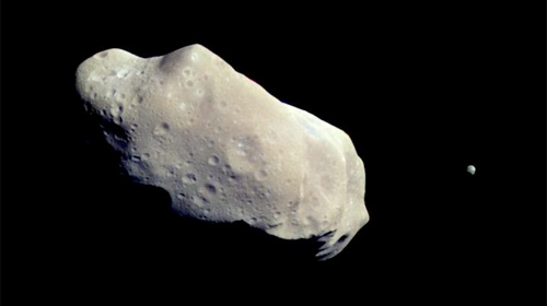 "According to former Nasa scientists, it's blind luck a populated are of earth hasn't been hit by an asteroid. Photo an asteroid called '243 Ida"" taken by the Galileo spacecraft. This asteroid is big enough to have its own moon (right): Wikipedia/Nasa"